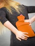 Κορίτσι που έχει τον πόνο στην πλάτη, που κρατά το μπουκάλι ζεστού νερού Στοκ εικόνες με δικαίωμα ελεύθερης χρήσης