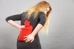 Κορίτσι που έχει τον πόνο στην πλάτη, που κρατά το μπουκάλι ζεστού νερού Στοκ Εικόνες