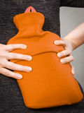 Κορίτσι που έχει τον πόνο στην πλάτη, που κρατά το μπουκάλι ζεστού νερού Στοκ Εικόνα