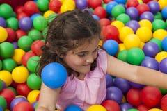 Κορίτσι που έχει το παιχνίδι διασκέδασης σε μια ζωηρόχρωμη πλαστική λίμνη σφαιρών Στοκ εικόνα με δικαίωμα ελεύθερης χρήσης