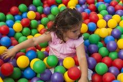 Κορίτσι που έχει το παιχνίδι διασκέδασης σε μια ζωηρόχρωμη πλαστική λίμνη σφαιρών Στοκ Φωτογραφία