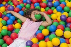Κορίτσι που έχει το παιχνίδι διασκέδασης σε μια ζωηρόχρωμη πλαστική λίμνη σφαιρών Στοκ φωτογραφία με δικαίωμα ελεύθερης χρήσης