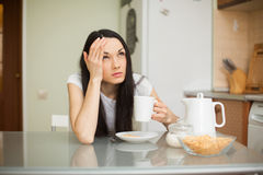Κορίτσι που έχει το πρόγευμα στην κουζίνα με τον πονοκέφαλο Στοκ φωτογραφίες με δικαίωμα ελεύθερης χρήσης