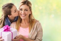Κορίτσι που δίνει το παρόν γενεθλίων στη μητέρα πέρα από τα φω'τα στοκ εικόνα