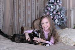 Κορίτσι που αγκαλιάζει τη γάτα της που βρίσκεται στο κρεβάτι Στοκ φωτογραφία με δικαίωμα ελεύθερης χρήσης