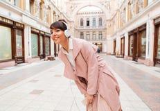 Κορίτσι που ακούει τη μουσική με τα ακουστικά σε μια οδό πόλεων Στοκ Εικόνα