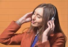 Κορίτσι που ακούει τη μουσική στα μεγάλα ακουστικά στοκ εικόνες
