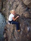 Κορίτσι που αναρριχείται επάνω σε έναν απότομο βράχο Στοκ Εικόνα