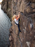 Κορίτσι που αναρριχείται επάνω σε έναν απότομο βράχο Στοκ Εικόνες