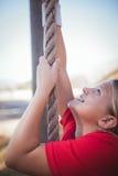 Κορίτσι που αναρριχείται σε ένα σχοινί κατά τη διάρκεια της κατάρτισης σειράς μαθημάτων εμποδίων Στοκ Φωτογραφίες