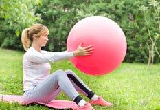 Κορίτσι που ανυψώνει fitball στον κήπο Στοκ Εικόνες