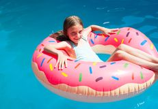 Κορίτσι που βάζει ζωηρόχρωμο διογκώσιμο doughnut Στοκ φωτογραφία με δικαίωμα ελεύθερης χρήσης