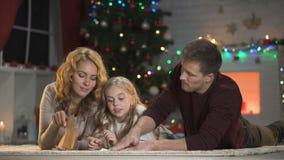 Κορίτσι που βάζει την επιστολή για Santa στο φάκελο, που βρίσκεται κάτω από το χριστουγεννιάτικο δέντρο με τους γονείς απόθεμα βίντεο