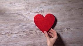 Κορίτσι που βάζει δύο κόκκινες καρδιές σε έναν ξύλινο πίνακα, τοπ άποψη Ημερομηνία, αγάπη, οικογενειακές έννοιες 4K βίντεο απόθεμα βίντεο