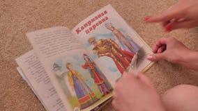 Κορίτσι που βγάζει φύλλα μέσω ενός ζωηρόχρωμου βιβλίου που βρίσκεται στο πάτωμα Γυρίζει τις σελίδες και εξετάζει το κείμενο train φιλμ μικρού μήκους