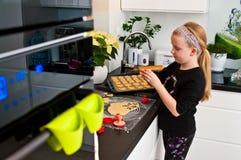 Κορίτσι που βοηθά με το μαγείρεμα Χριστουγέννων πιπεροριζών Στοκ Εικόνες