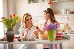 Κορίτσι που βοηθά το mom της στη ζωγραφική των αυγών Πάσχας Στοκ Εικόνες