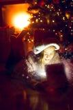 Κορίτσι που βρίσκεται κάτω από το χριστουγεννιάτικο δέντρο και που κοιτάζει στο λαμπιρίζοντας δώρο BO Στοκ φωτογραφία με δικαίωμα ελεύθερης χρήσης
