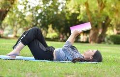 Κορίτσι που βρίσκεται στη χλόη και το διαβασμένο βιβλίο Στοκ φωτογραφία με δικαίωμα ελεύθερης χρήσης