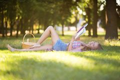 Κορίτσι που βρίσκεται στη χλόη και την ανάγνωση Στοκ φωτογραφία με δικαίωμα ελεύθερης χρήσης