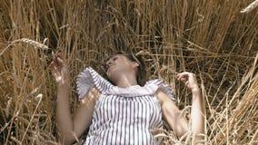 Κορίτσι που βρίσκεται στο έδαφος στον τομέα σίτου απόθεμα βίντεο