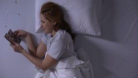 Κορίτσι που βρίσκεται στο κρεβάτι που εξετάζει τη λυσσασμένη φωτογραφία του φίλου της, σκληρή αποσύνθεση απόθεμα βίντεο
