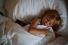 Κορίτσι που βρίσκεται στο κρεβάτι μετά από τον ύπνο ξύπνημα πρωινού, ένα πρωί διασκέδασης, που παίζει στο κρεβάτι στοκ εικόνα