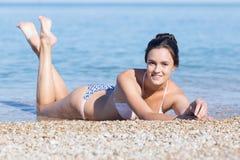 Κορίτσι που βρίσκεται στο μέτωπο στα χαλίκια κοντά στη θάλασσα στοκ φωτογραφία