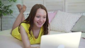 Κορίτσι που βρίσκεται στο σπίτι στο κρεβάτι με το lap-top απόθεμα βίντεο