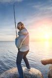 Κορίτσι που γαντζώνει ένα ψάρι στην ακτή της λίμνης Στοκ εικόνες με δικαίωμα ελεύθερης χρήσης