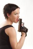 Κορίτσι που γλείφει το πυροβόλο όπλο της Στοκ Εικόνες