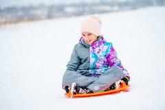 Κορίτσι που γλιστρά κάτω από το λόφο στο έλκηθρο πιατακιών στοκ φωτογραφίες με δικαίωμα ελεύθερης χρήσης