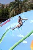 Κορίτσι που γλιστρά στην υγρή λίμνη παιχνιδιών φυσαλίδων Στοκ Εικόνες