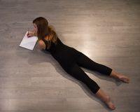 Κορίτσι που γράφει σε ένα σημειωματάριο στο πάτωμα στοκ εικόνες