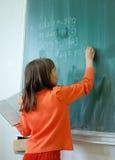 Κορίτσι που γράφει στο σχολικό χαρτόνι Στοκ φωτογραφία με δικαίωμα ελεύθερης χρήσης