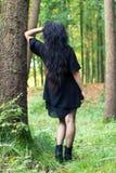 Κορίτσι που γυρίζουν γύρω από τη στάση και την κλίση σε ένα δέντρο Στοκ φωτογραφίες με δικαίωμα ελεύθερης χρήσης