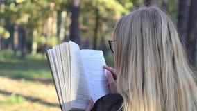 Κορίτσι που διαβάζει ένα βιβλίο στο δάσος απόθεμα βίντεο