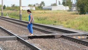 Κορίτσι που διασχίζει τις σιδηροδρομικές γραμμές απόθεμα βίντεο