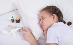 Κορίτσι που είναι άρρωστο και βρίσκεται στο κρεβάτι, κοντά σε ένα σύνολο χαπιών και mextures στοκ εικόνες