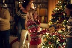 Κορίτσι που εκπλήσσει το κορίτσι φίλων της με ένα παρόν με τα Χριστούγεννα Έννοια των Χριστουγέννων εορτασμού και του νέου έτους στοκ εικόνα με δικαίωμα ελεύθερης χρήσης