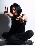 κορίτσι που εμφανίζει στο σημάδι καθιερώνουσα τη μόδα νίκη Στοκ Εικόνα