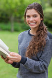 Κορίτσι που εξετάζει τη κάμερα διαβάζοντας ένα βιβλίο Στοκ εικόνα με δικαίωμα ελεύθερης χρήσης