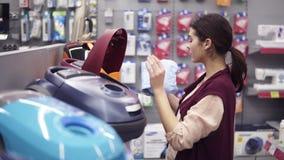 Κορίτσι που επιλέγει την ηλεκτρική σκούπα στο κατάστημα συσκευών Ερχομός μέχρι μια σειρά επίδειξης που παίρνει dustbag από την ηλ φιλμ μικρού μήκους