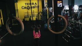 Κορίτσι που επιλύει με τα γυμναστικά δαχτυλίδια στη γυμναστική crossfit φιλμ μικρού μήκους