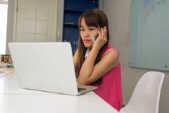 Κορίτσι που εργάζεται στο lap-top και που απαντά στην κλήση στοκ φωτογραφία