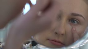 Κορίτσι που εφαρμόζει την κρέμα ματιών που κοιτάζει στον καθρέφτη, πρώτες ρυτίδες, φροντίδα δέρματος, νεολαία απόθεμα βίντεο