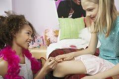 Κορίτσι που εφαρμόζει το καρφί στίλβωση στα νύχια του φίλου στοκ εικόνα