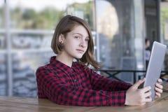 Κορίτσι που θέτει υπαίθρια να χρησιμοποιήσει το PC ταμπλετών στοκ εικόνα