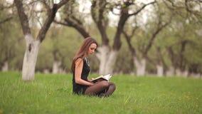 Κορίτσι που διαβάζει ένα βιβλίο στον πράσινο χορτοτάπητα απόθεμα βίντεο