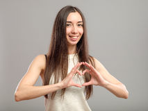 Κορίτσι που διαμορφώνει την καρδιά με τα χέρια της Στοκ Φωτογραφία
